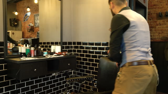 Hairdresser turning and leaning on barber chair video