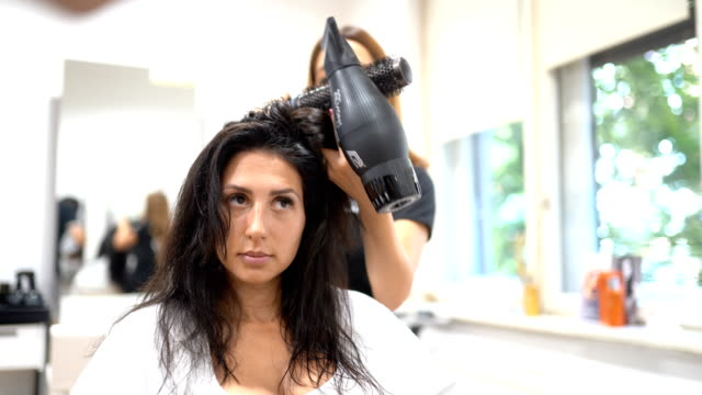 Hairdresser using hairdryer and brushing hair