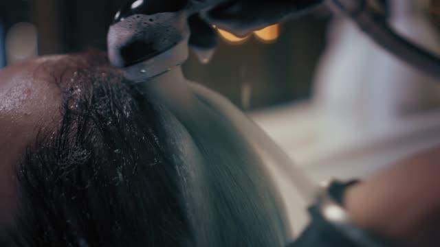 vídeos y material grabado en eventos de stock de larga rubia peluquería wahes mujer con champú en el fregadero en el salón de belleza. closeup - salón de belleza