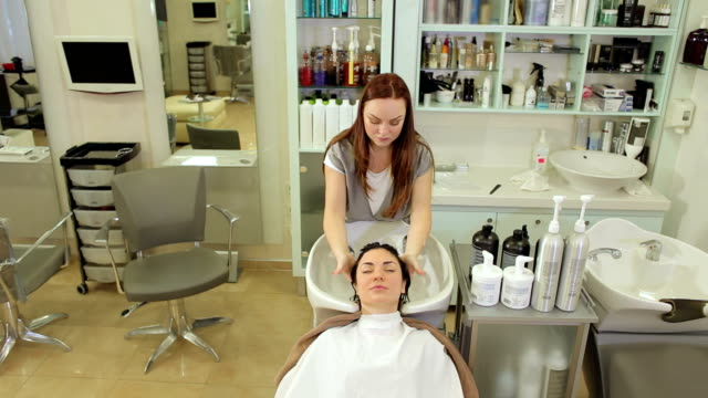 Hairdresser washes the hair of a young girl before a haircut in a beauty salon. Professional hairdresser washes her hair and gives a head massage for a young fashionable girl. The girl enjoys the procedure of washing the head and massage while lying in special hairdressing chair. beauty salon stock videos & royalty-free footage