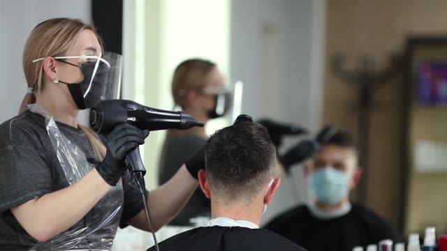 vidéos et rushes de coiffeur avec des mesures de sécurité pour covid-19, sèche-cheveux un homme dans un masque de médecine, distance sociale, coupe des cheveux avec un masque médical, bouclier facial et gants en caoutchouc dans un salon de beauté - coiffeur