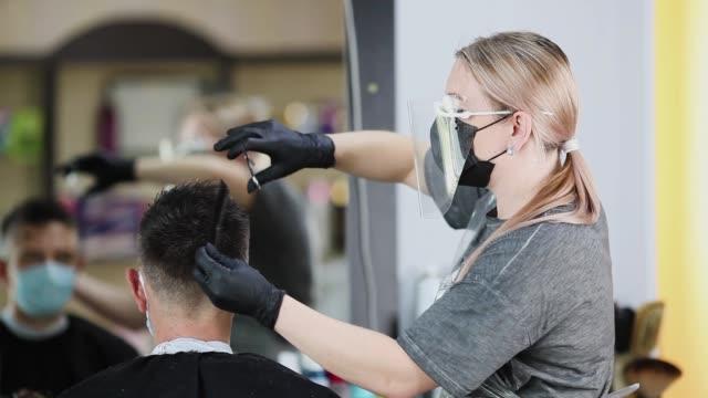 vidéos et rushes de un coiffeur avec des mesures de sécurité pour covid-19, coupe un homme dans un masque médical avec un ciseaux, distance sociale, couper les cheveux avec un masque médical, un masque de protection et des gants en caoutchouc dans un salon de beauté - coiffeur