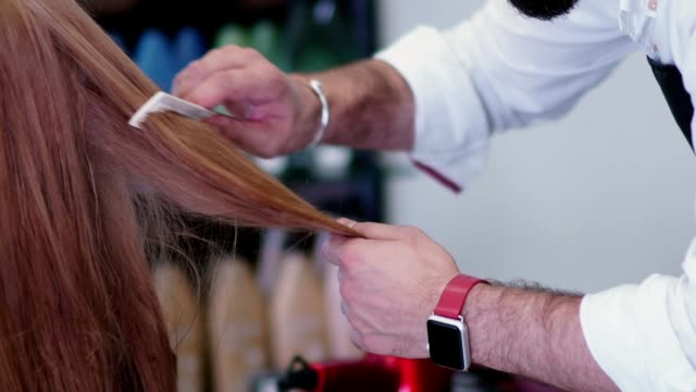 Hairdresser works. Hands male stylist. Comb the hair ends video