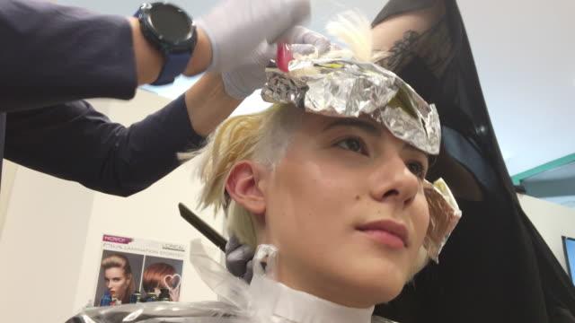friseure kooperieren sterbende haare einer jungen frau - haartönung stock-videos und b-roll-filmmaterial