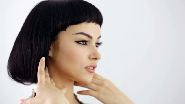 Hairstyle preparations. Cleopatra's make-up and haircut posing in studio High fashion look. Glamorous closeup portrait of beautiful sexy stylish brunette young woman model corrects a hairstyle against bright gray background. Cleopatra hairstyle stock videos & royalty-free footage