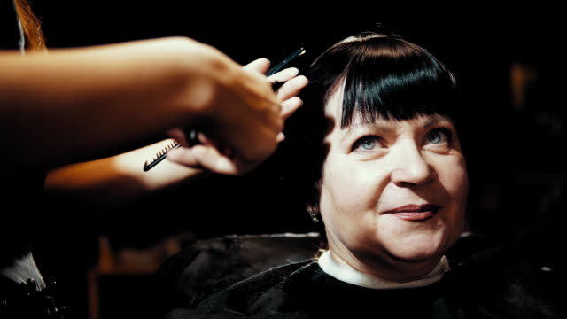 hairstylist cut female hair during haircutting in hairdressing salon. - forbici video stock e b–roll