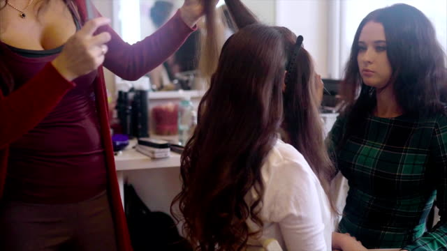 Hairstylist making hair-do while make up artist applying eyeshadows slow motion. video