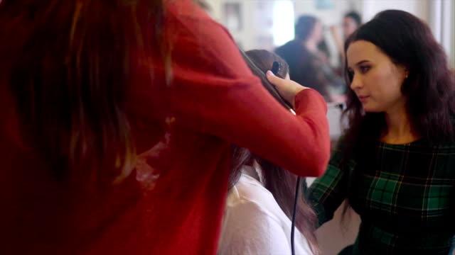 Coiffeur qui sèche-faire avec le fer à lisser tout maquilleur application cosmétique - Vidéo