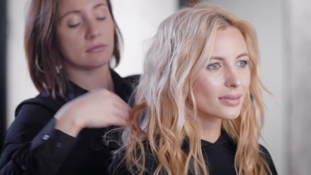 vidéos et rushes de femme de coiffeur corrige les écluses sur la tête du client adulte blonde de salon de coiffure, faire style - soins capillaires