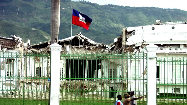 Haitian Flag Flying Over the Ruined Presidential Palace The Haitian Flag flapping in the breeze over the ruined Presidential Palace with green hills in the background and cars and people in the foreground earthquake stock videos & royalty-free footage