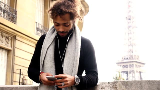 Half Nigerian boy typing message and listening to music near Eiffel tower video