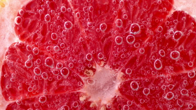 Half of a ripe grapefruit under water with air bubbles.