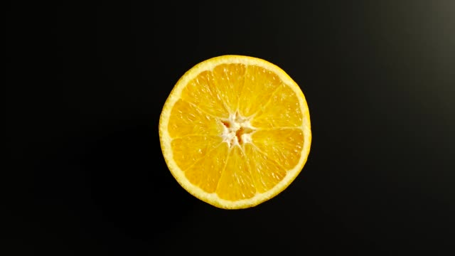 top view: half of an orange rotates on a black surface - stop motion - rotolare video stock e b–roll
