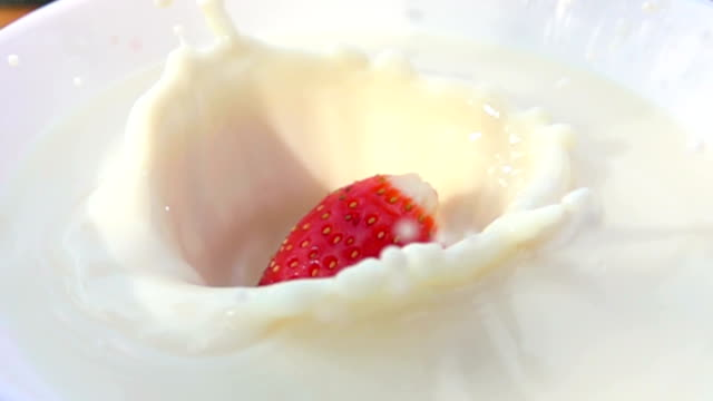 Half of strawberry falling in a bowl with cream video