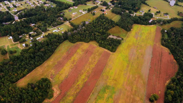A Half Plowed Field That is Brown and Green and Surrounded by Trees video