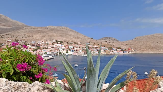 halki ( chalki ) island in the aegean sea, cactus plants against beautiful city with white houses built on rustic mountain at the edge of blue sea - isole egee video stock e b–roll