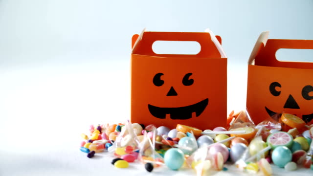 Halloween box with various candies on white background 4k video