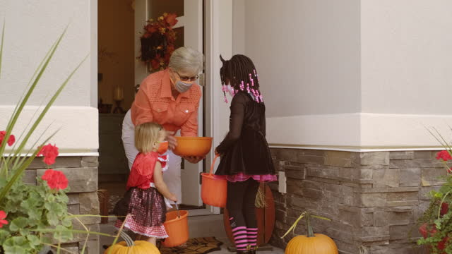 Halloween Children Trick or Treating Wearing Facemasks Children trick or treating on Halloween wearing facemarks for protection. halloween covid stock videos & royalty-free footage