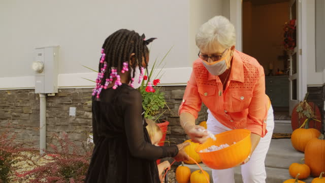 vídeos de stock, filmes e b-roll de crianças de halloween truque ou tratamento usando máscaras faciais - halloween