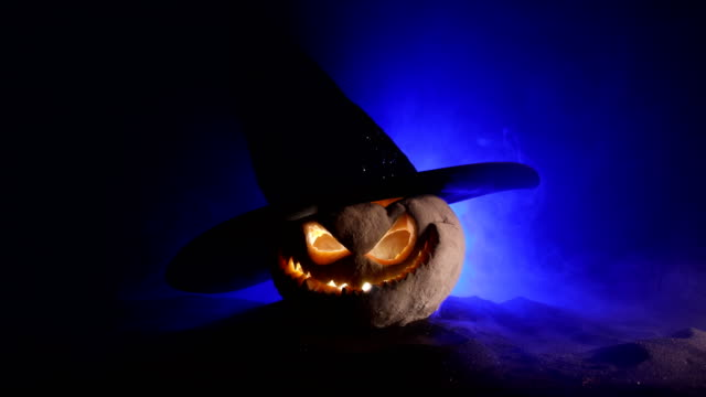 halloween concept. jack-o-lantern smile and scary eyes for party night. close up view of scary pumpkin with witch hat on at dark foggy background. selective focus. empty space - zucca legenaria video stock e b–roll