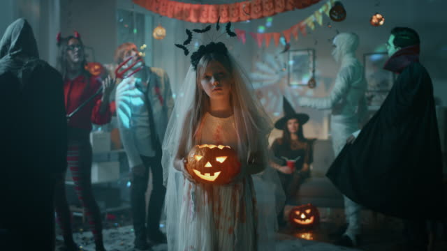 halloween costume party: little girl in a bloody white bride dress holding scary doll. zombie, blood thirsty dracula, mummy, bewitching witch and dazzling she devil having fun in decorated room - halloween video stock e b–roll