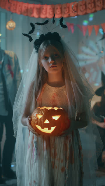 Halloween Costume Party: Little Girl in a Bloody White Bride Dress Holding Scary Pumpkin Head with Candle Inside. Vertical Screen Orientation Video 9:16