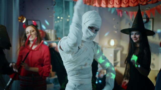 Halloween Costume Party: Old Skinny and Bandaged Mummy Dances. In the Background Zombie, Death, Witch and She Devil Have Fun in a Monster Party Decorated Room Halloween Costume Party: Old Skinny and Bandaged Mummy Dances. In the Background Zombie, Death, Witch and She Devil Have Fun in a Monster Party Decorated Room. Shot on RED EPIC-W 8K Helium Cinema Camera. vampire stock videos & royalty-free footage