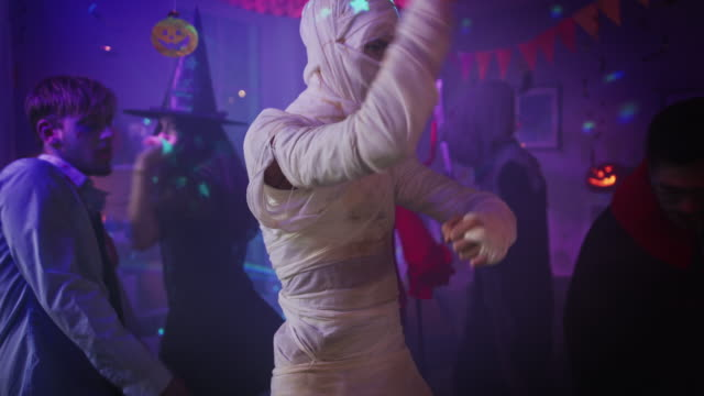 halloween costume party: old skinny and bandaged mummy dances. in the background zombie, death, witch and she devil have fun in a monster party decorated room - halloween video stock e b–roll