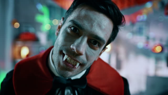 Halloween Costume Party: Portrait of Count Dracula Smiling Creepily, Showing His Deadly Bloody Fangs, Does His Deadly Bite. In the Background Thematically Decorated Neon Colorful Room Halloween Costume Party: Portrait of Count Dracula Smiling Creepily, Showing His Deadly Bloody Fangs, Does His Deadly Bite. In the Background Thematically Decorated Neon Colorful Room. Shot on RED EPIC-W 8K Helium Cinema Camera. count dracula stock videos & royalty-free footage