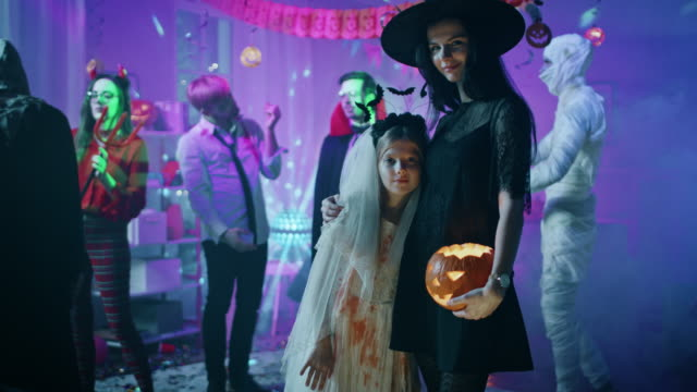 Halloween Costume Party: Portrait of Dazzling Young Witch Holding Burning Pumpkin Head Standing with Smiling Little Girl in a Bloody White Bride Dress. Cool Monster Party with Disco Ball Lights