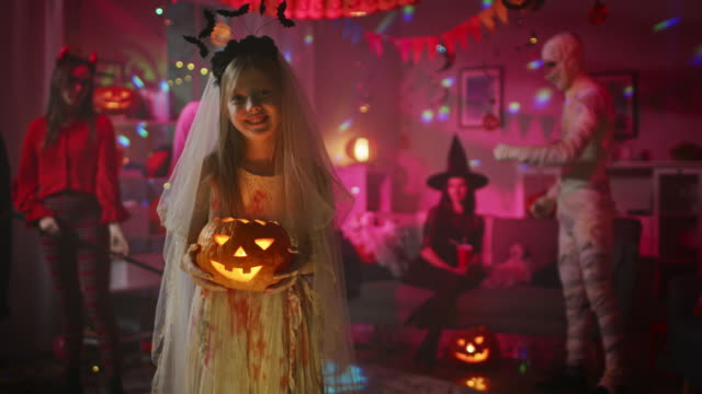Halloween Costume Party: Smiling Little Girl in a Bloody White Bride Dress Holding Burning Pumpkin Head. Zombie, Blood Thirsty Dracula, Mummy, Bewitching Witch and Dazzling She Devil Dance