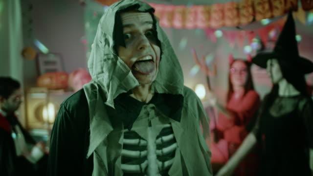 festa in costume di halloween: terrificanti salti di morte urlanti spaventa newhere. nello sfondo zombie, morte, strega, mummia e lei diavolo si divertono in una stanza decorata monster party - decorazione festiva video stock e b–roll