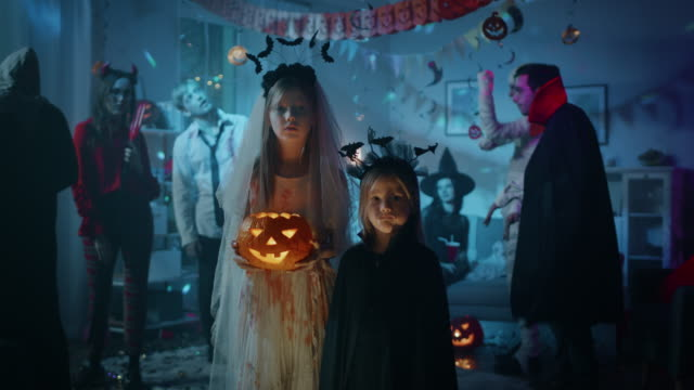Halloween Costume Party:Portrait Girl in a Bloody White Bride Dress Holding Scary Doll Standing with Cute Little Vampire Bat Sister. In the Background Group of Monsters Dancing and Having Fun