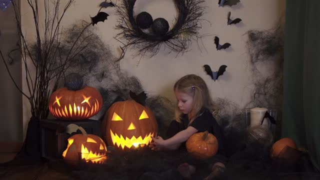 Halloween girl paints a pumpkin. A child in a web is preparing for the holiday.
