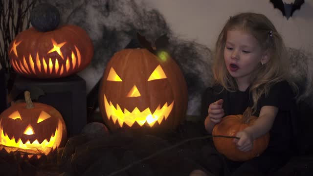 Halloween girl says witchcraft. Magic wand and pumpkin. Child for holiday. kids