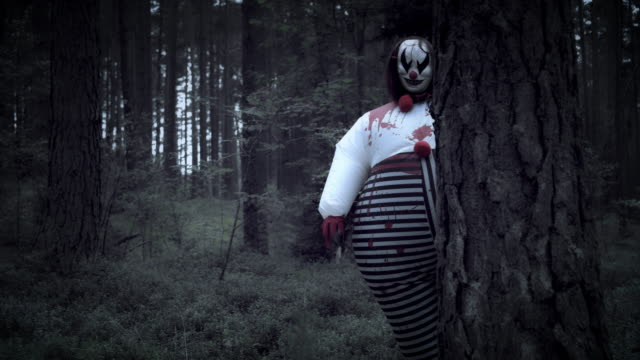 4K Halloween Horror Clown in Forest Behind a Tree video