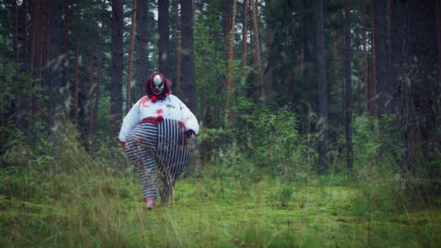 4K Halloween Horror Clown in Forest Walking Inspired from horror movies playing card stock videos & royalty-free footage