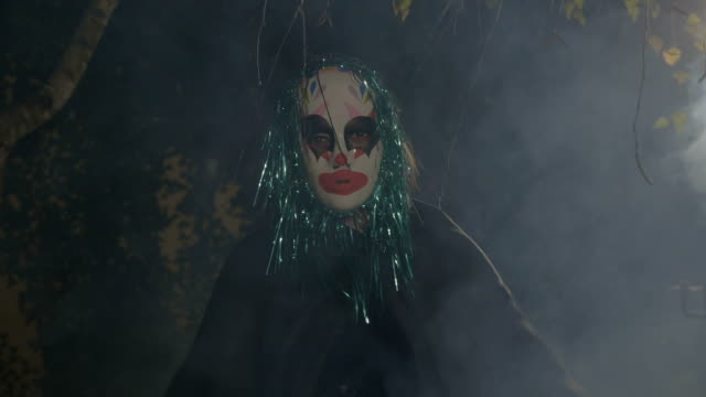Halloween horror clown sitting in darkness outside in smoke performing a dancing death ritual and evil laughing video