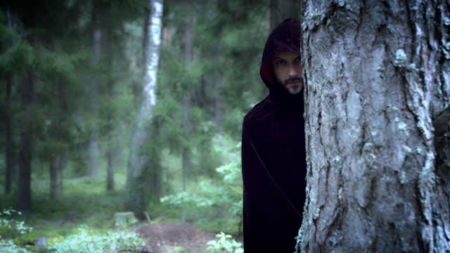 vidéos et rushes de 4k halloween horreur homme qui se cache dans les bois avec cape noire - charmeur