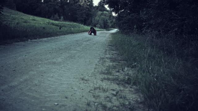 4K Halloween Horror hombre con máscara de cerdo arrastrándose en el camino - vídeo