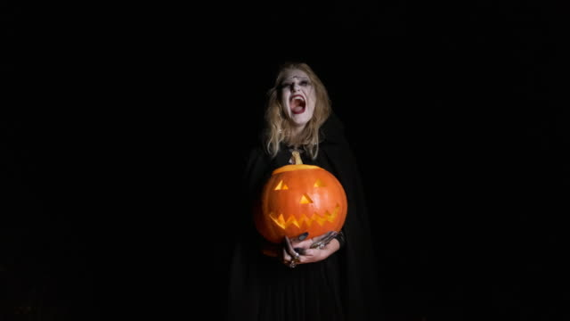 halloween image .young witch in black clothes holds pumpkin in her hands. - top nero video stock e b–roll