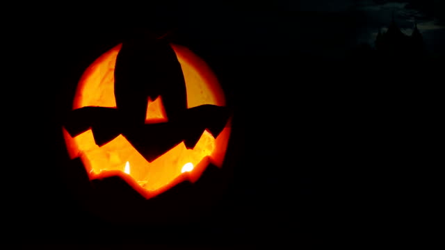 Halloween Jack-o'-lantern face with old horor castle with sparks on the background video