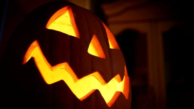 a halloween jack-o-lantern pumpkin lights up inside a home - halloween стоковые видео и кадры b-roll