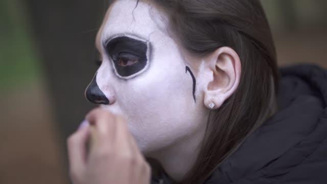 Halloween. Makeup artist applies make-up to female face