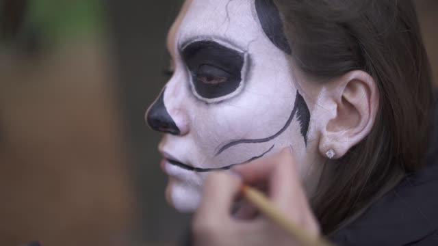 Halloween. Makeup artist applies make-up to girl face