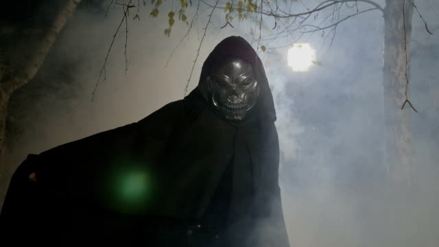 Halloween movie scene with an adult wearing a skelton mask and mantle frightening the camera in a foggy forest video