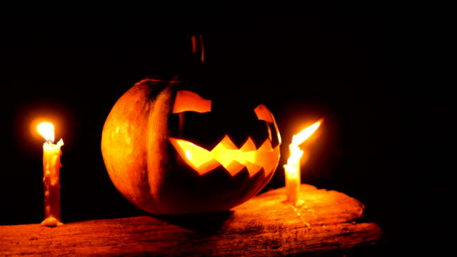 Halloween Pumpkin Jack-o-lantern with Candles on Tree Trunk in the Night, Dolly shot video