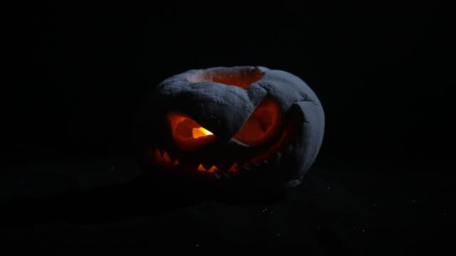 halloween pumpkin smile and scary eyes for party night. close up view of scary halloween pumpkin with eyes glowing inside at black background. selective focus - zucca legenaria video stock e b–roll