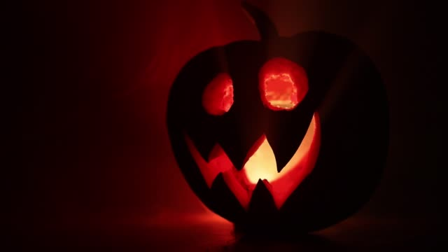 halloween pumpkin smile and scrary eyes for party night. close up view of scary halloween pumpkin with eyes glowing inside at black background. selective focus - zucca legenaria video stock e b–roll