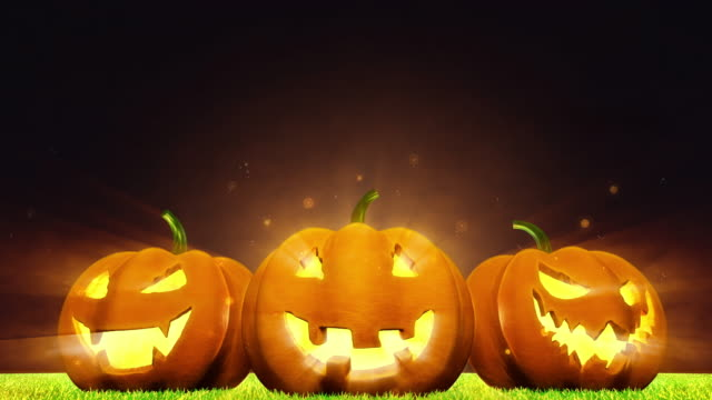 Halloween pumpkin with ghost face on grass with light ray, magic dust and night sky